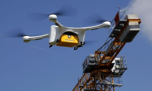 A drone containing laboratory samples flies in front of crane during a trial flight.